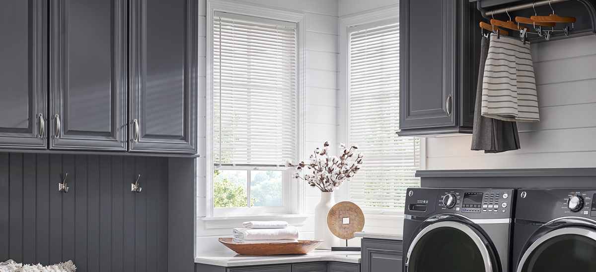 white aluminum blinds in laundry room with grey cabinetry